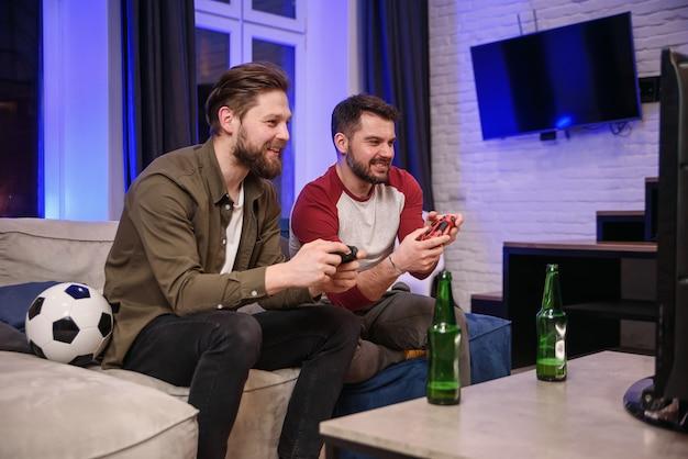Замедленное движение эмоциональных возбужденных забавных молодых многонациональных парней, которые обманывают друг друга, играя в видеоигры дома, один бородатый парень празднует победу, второй теряет