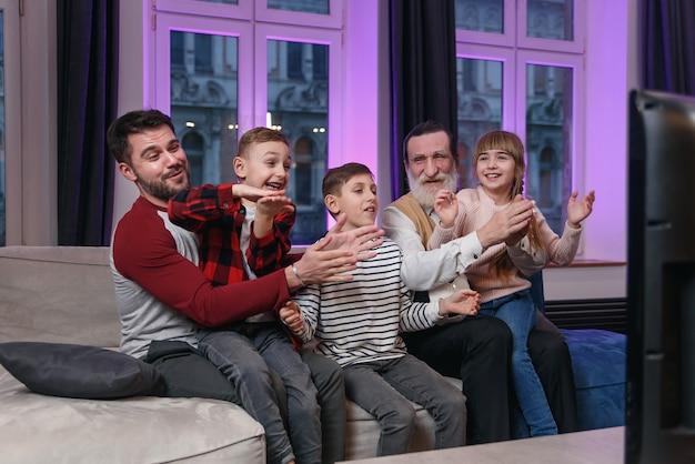 Счастливая дружная семья смотрит футбольный матч, чемпионат на диване у себя дома. болельщики эмоционально болеют за любимую сборную. папа, дедушка и внуки. спорт, телевидение, веселье.