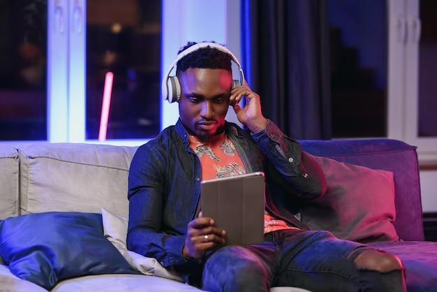 Красивый радостный стильный афроамериканец с наушниками на шее отдыхает на мягком диване у себя дома и просматривает приложения на планшетном пк с счастливой улыбкой
