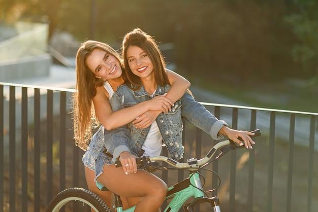 自転車に座っていると日没の背景に素敵な笑顔でカメラを見て彼女の魅力的な女友達を抱き締める豪華な陽気な若い女性