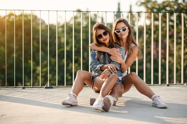 サングラスとスケートボードの上に座って、街並みの背景に抱いてスタイリッシュな流行の服で陽気な魅力的な女の子。