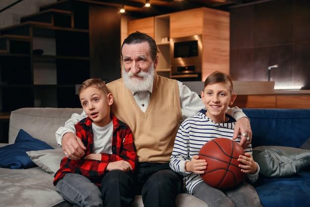 Мальчики на диване с дедушкой болеют за баскетбольный матч и держат баскетбольный мяч. огромные спортивные фанаты.