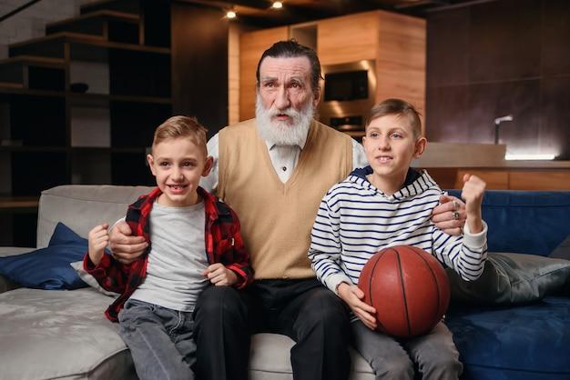 彼らの祖父がバスケットボールの試合を応援し、バスケットボールのボールを保持しているソファに座っている男の子。巨大なスポーツ狂。