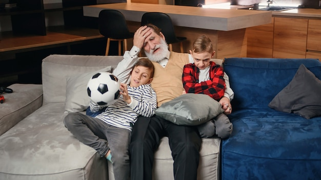 Возбужденные три поколения поклонников мужского спорта отдыхают в гостиной, вместе празднуют командную победу, веселый маленький мальчик с папой и дедушкой весело проводят время, наблюдая футбольный матч дома вместе
