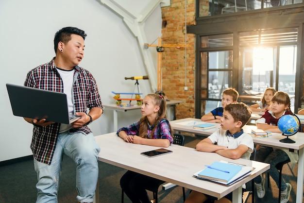Молодой корейский мужской учитель, сидя на столе с ноутбуком, давая урок для шести учеников начальной школы.