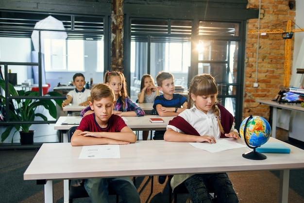 机に座って、現代のスマートスクールの教室で試験に合格する小学生のグループ。