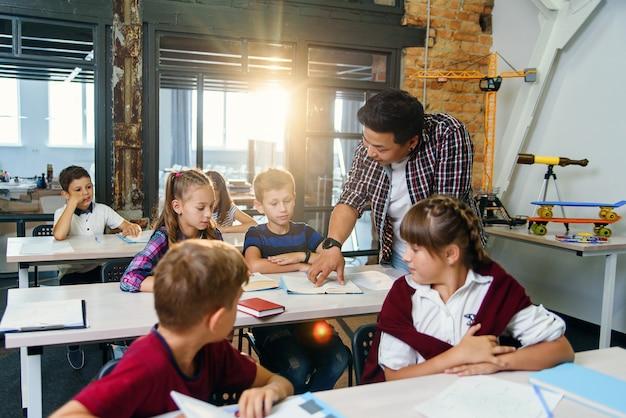 Учитель помогает школьникам с тестовыми заданиями в классе в начальной школе.