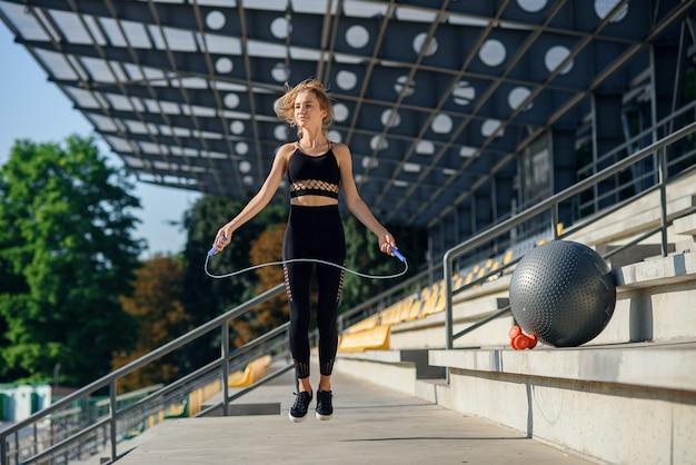 スタジアムで縄跳びでジャンプの女性。屋外の演習を行うアクティブなフィットネス女性。