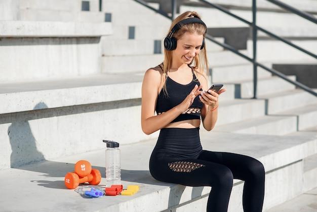 Красивая фитнес-девушка в серой спортивной одежде использует смартфон и слушает музыку на стадионе после тренировки.