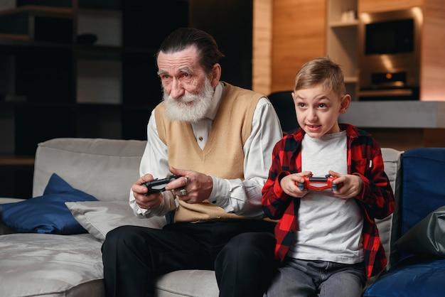 Милый маленький мальчик с дедом, сидя на диване и играть в видеоигры с игровой площадкой