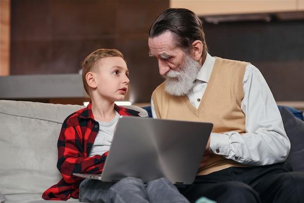 Внук учит своего деда пользоваться ноутбуком