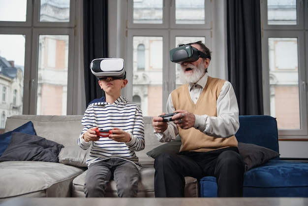 Дед и внук играют в видеоигры на компьютере за столом ночью дома