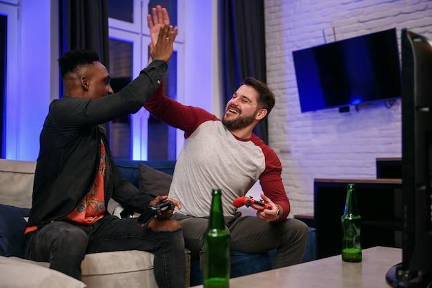 Друзья дома играют в видеоигры, сидя на диване с контроллерами