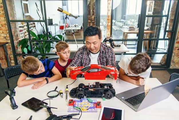Молодой корейский инженер-электронщик с маленькими детьми с помощью отвертки разбирает роботизированную машину за столом в современной школе. замедленное движение