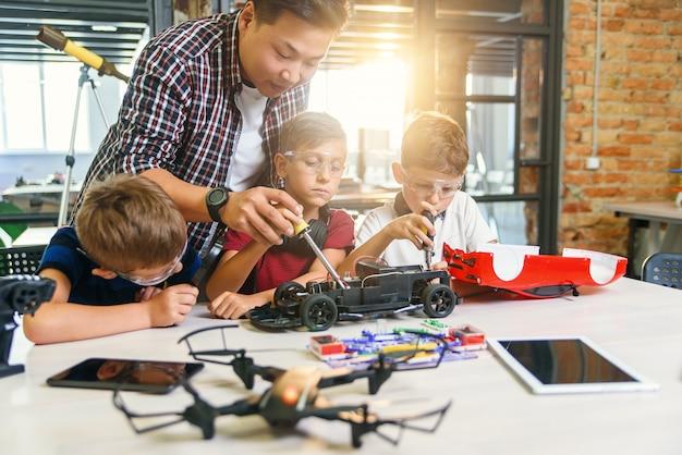 スマートスクールラボで働くヨーロッパの小学生とラジコン電気自動車のテストモデルを持つ男性の電子エンジニア。
