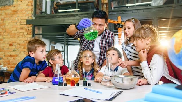 Ученики начальной школы внимательно следят за своим учителем, который показывает интересные химические эксперименты с цветными жидкостями в стеклянных колбах.