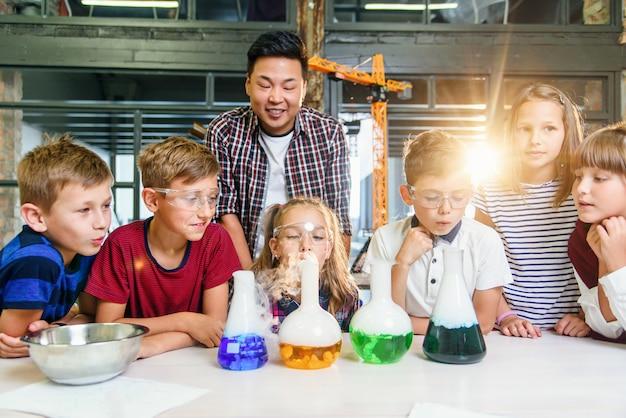 Школьники с молодыми учителями-мужчинами на уроке химии проводят интересные эксперименты с использованием химических жидкостей и сухого льда в современном лабораторном классе.
