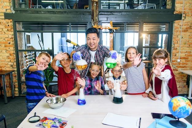 Азиатский учитель делает эксперименты с сухим льдом для детей в классе в современной школе. во время эксперимента ученый держит колбу с реакционной дымкой и цветной жидкостью.