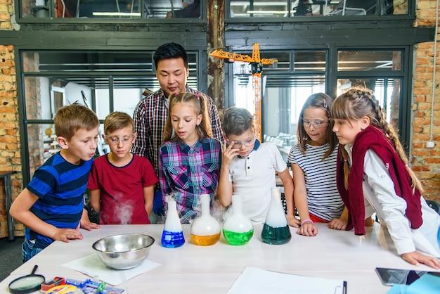 Молодой учитель-мужчина объясняет ученикам реакцию испарения, используя цветную воду и сухой лед на уроке химии.