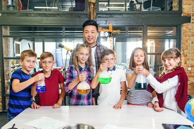 Корейский учитель с группой из шести веселых молодых кавказских учеников, носящих очки во время химического эксперимента в современной школе, держит тестовое стекло с цветной жидкостью.