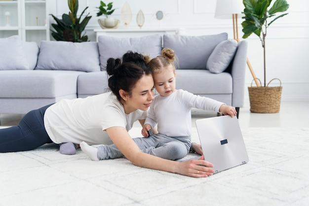 若い母親と彼女の愛らしい娘は床に横たわっている間ラップトップを使用しています。