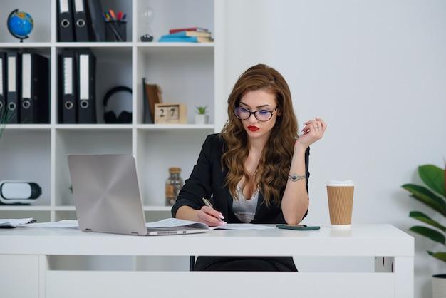 スタイリッシュな服を着ているオフィスで美しいビジネス女性は、モダンな居心地の良いオフィスに座っている間、紙にいくつかのメモを作ります。