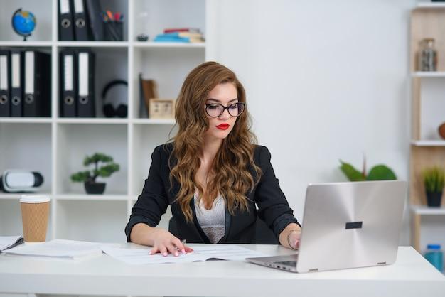 Привлекательная коммерсантка сидя на столе в уютном ярком офисе и работая с портативным компьютером.