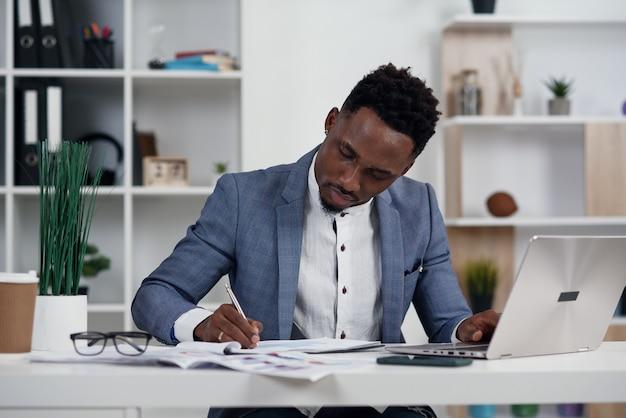 ラップトップを持ったビジネスマン。若いアフリカの実業家は彼のオフィスのラップトップで何かを入力しています。