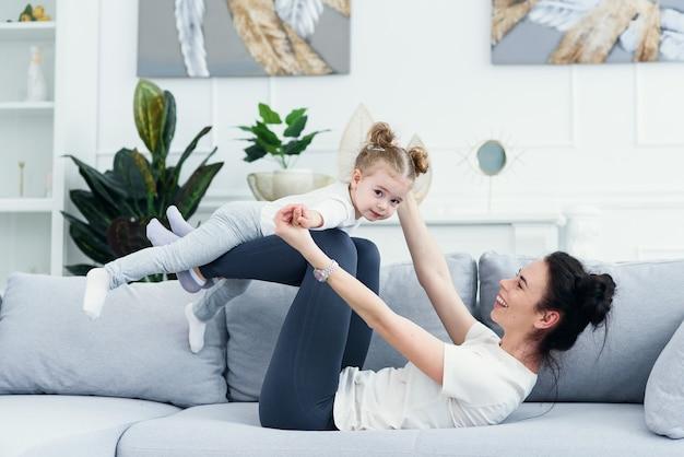 Мама и ее дочь лежат на диване в гостиной.
