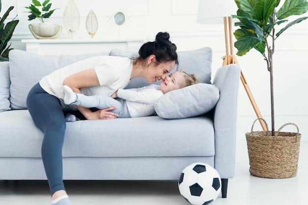 ママと娘がリビングルームのソファに横になっています。