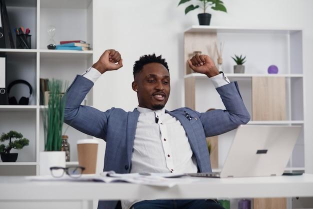 Темнокожий мужчина с легкой улыбкой сложил руки за головой и смотрит на свой ноутбук в современном офисе.