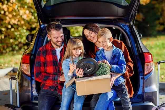 かわいい子供たちがトランクに座っていると植物のカートンボックスを保持している素敵な若い親