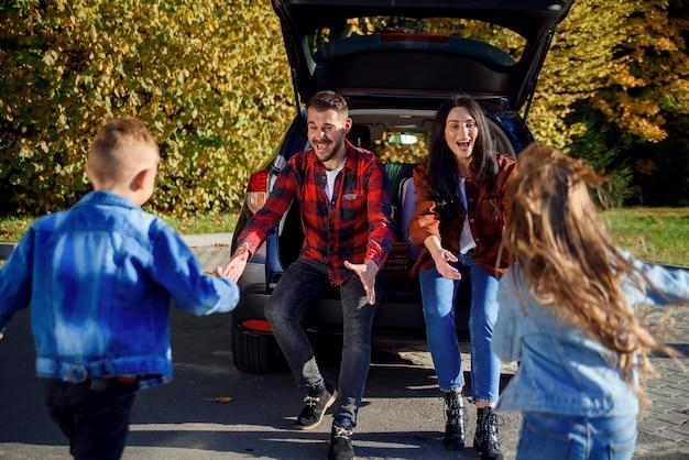 車のトランクに座っている若い親が幸せな息子と娘を抱きしめる