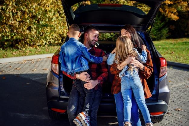 車のトランクに座って幸せな陽気な若い親と幸せな子供たちを抱きしめる