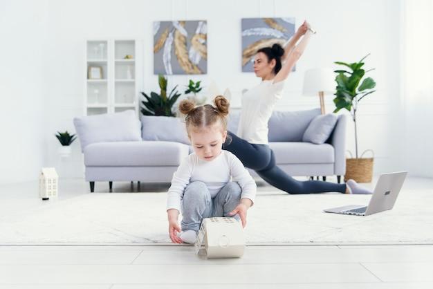 彼女のスポーティなママが背景にフィットネスとヨガの練習をしている間、家で遊んで面白い赤ちゃん女の子。