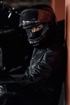 Женщина-мотоциклист за рулем своего эндуро мотоцикла или вертолета в стильной кожаной одежде и защитном снаряжении