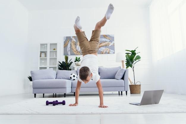 Счастливый мальчик гимнастическая акробатика поза равновесия на белом фоне