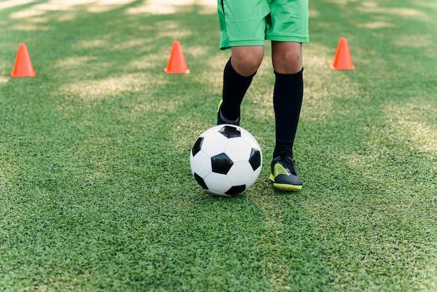 Закройте ноги и ноги футболиста на зеленой траве