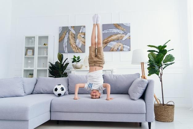 スポーティなアクロバット少年が自宅のソファの上の彼の頭の上に立っています。