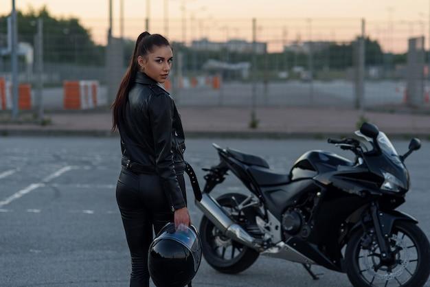 夕暮れ時のスタイリッシュなスポーツバイクの屋外駐車場で黒い革のジャケットとフルフェイスのヘルメットを保持しているパンツで美しい少女の背面図。自由のライフスタイルのコンセプト。