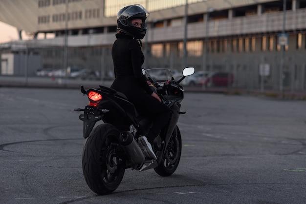 黒のタイトなボディスーツとフルフェイスヘルメットの愛らしい少女は、夜の都市の屋外駐車場でスタイリッシュなバイクに乗る。自由とアクティブなライフスタイルのコンセプト。完全に黒。