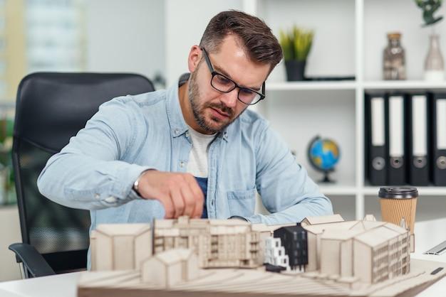 Красивый кавказский старший архитектор в очках работает над строительным проектом и рассматривает модель, над которой он работает.