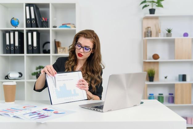スタイリッシュな服と眼鏡でビデオ通話で彼女のビジネスパートナーと話している自信を持って経験豊富な成功したビジネスウーマンとグラフでレポートを示しています。
