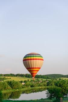自然の中でバルーニング。水に近い湖の上を飛んでいる美しい熱気球。