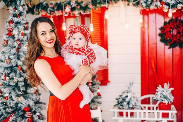 クリスマスツリーと花輪で飾られた休日の部屋でドレスの彼の小さな娘と赤いドレスで幸せな母