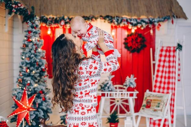 印刷された鹿とクリスマスツリーと花輪で飾られた部屋で雪の結晶と休日の服で彼の小さな娘と幸せな母
