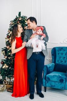 幸せな親とクリスマスの装飾が施された部屋で一緒にエレガントな服の小さな赤ちゃん。