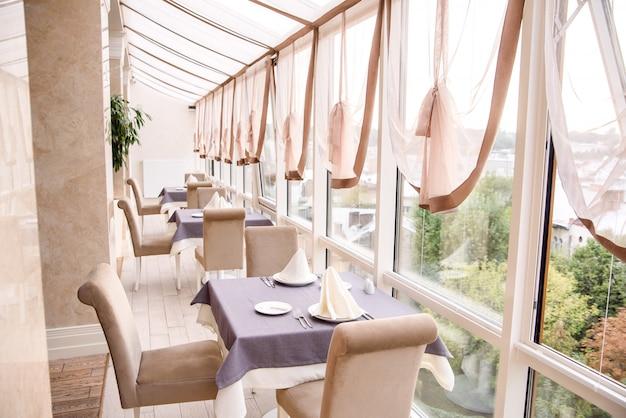 大きなパノラマの窓があるファッショナブルで高価なヨーロッパのレストランの明るいインテリア