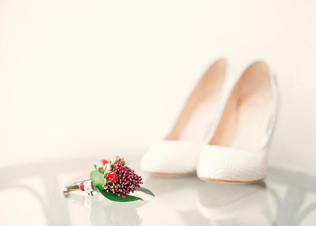 Белая свадебная обувь невесты и букет жениха на переднем плане