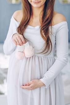 ベビーシューズを保持している白いドレスで美しい妊娠中の女性